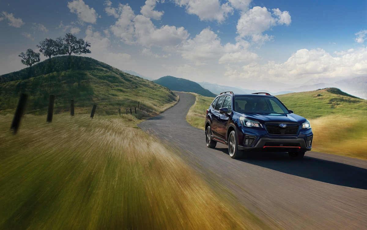 A 2021 Subaru Forester Sport driving on a country road.
