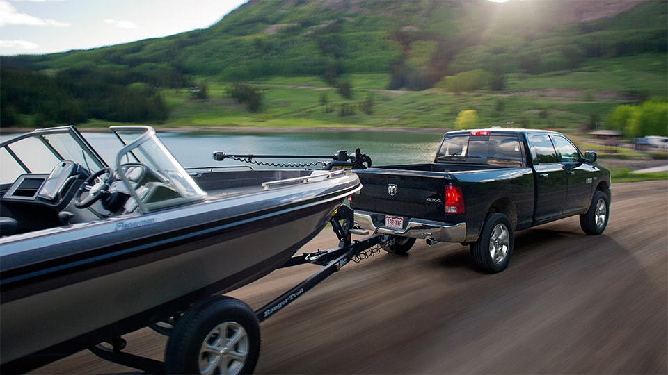 Green Ram 1500 truck towing a boat around Alaska