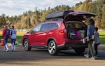 A family taking gear from the Power Rear Gate of their Subaru Ascent.