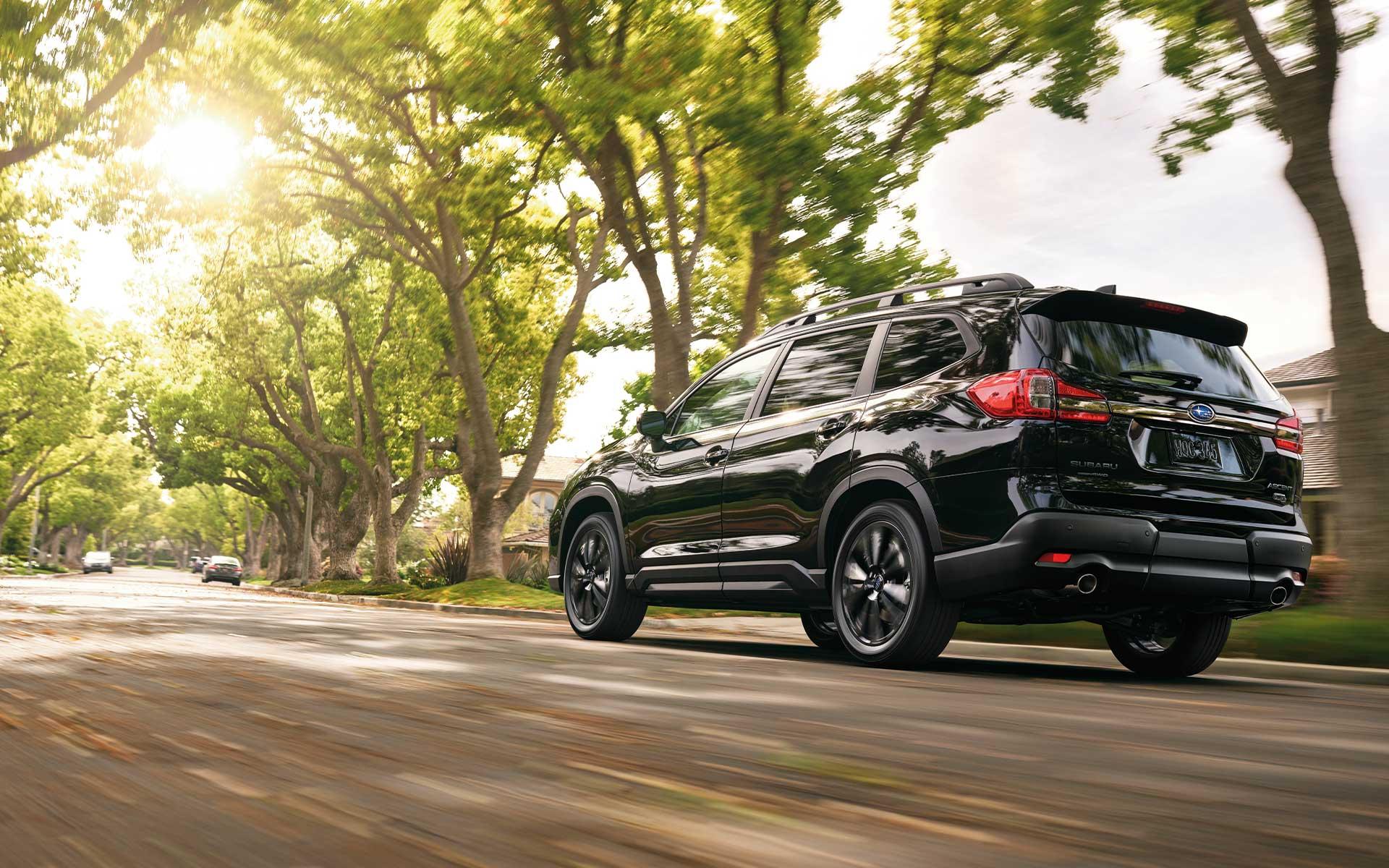 A Subaru Ascent Onyx Edition driving through a neighborhood.