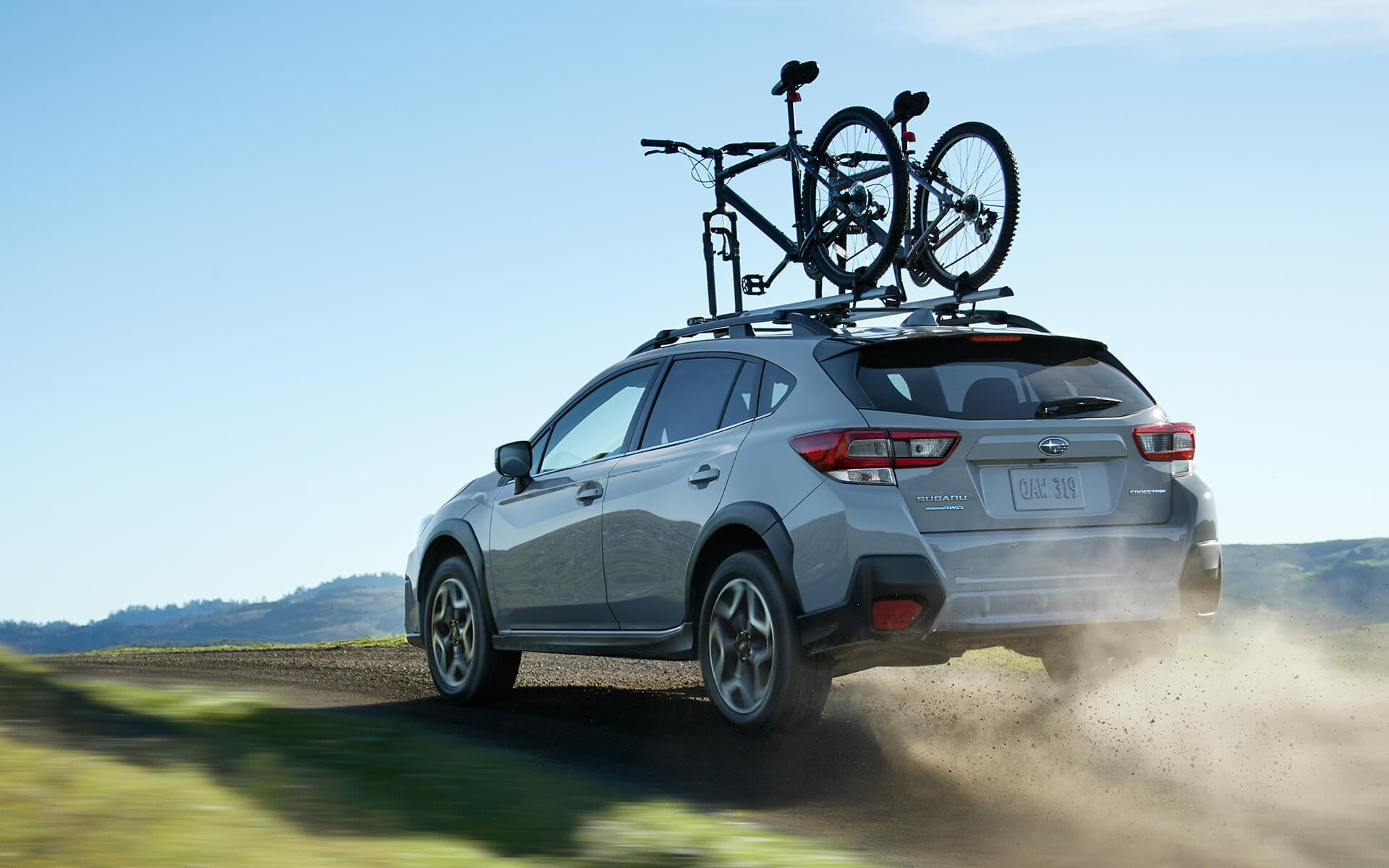 A 2020 Crosstrek with mountain bikes mounted to a rack accessory on its raised roof rails drives down a rough road in the wilderness.