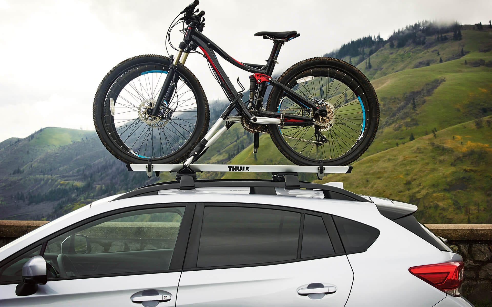 A 2020 Crosstrek with mountain bikes mounted to a rack accessory on its raised roof rails parked in the country