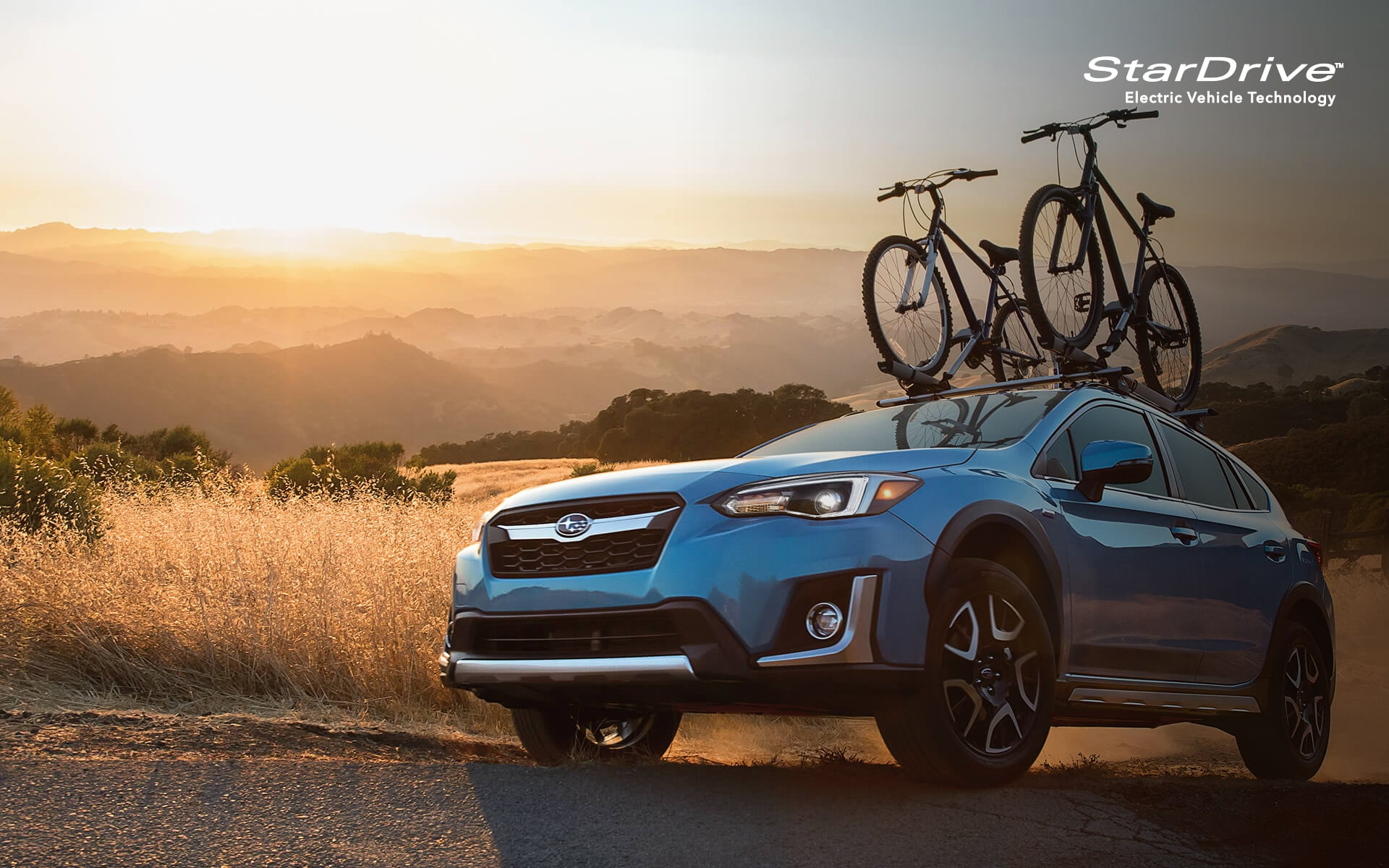 A 2020 Crosstrek Hybrid with mountain bikes mounted to its raised roof rails driving down a rough country road.