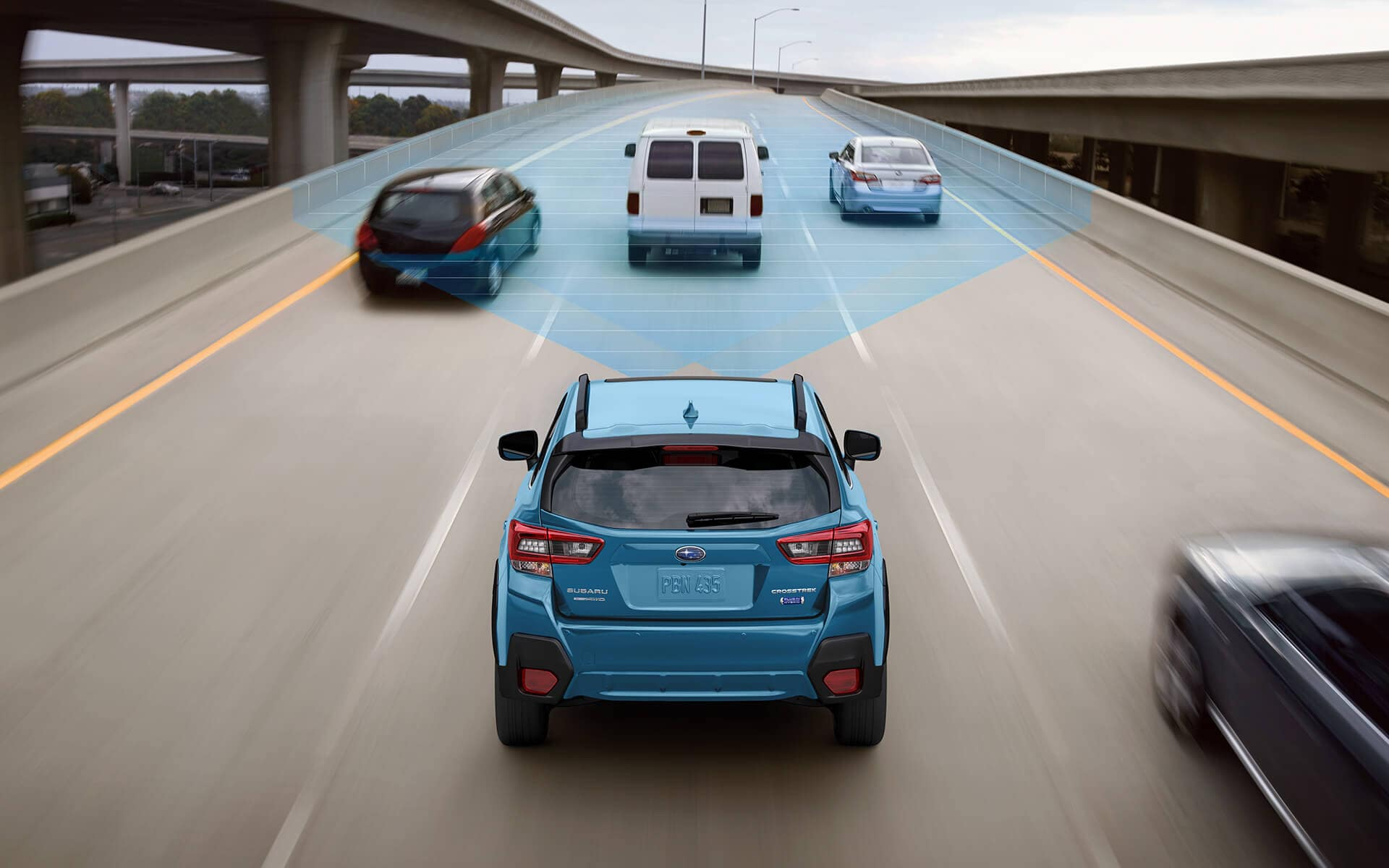 A 2020 Crosstrek Hybrid driving on a freeway with the EyeSight® Driver Assist Technology sensors illustrated with blue overlay.