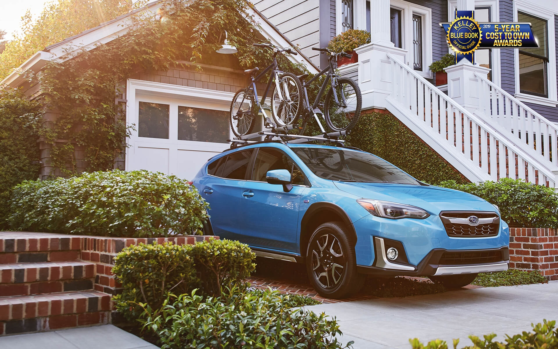 A 2020 Crosstrek Hybrid with mountain bikes mounted to a rack accessory on its raised roof rails parked in a driveway.