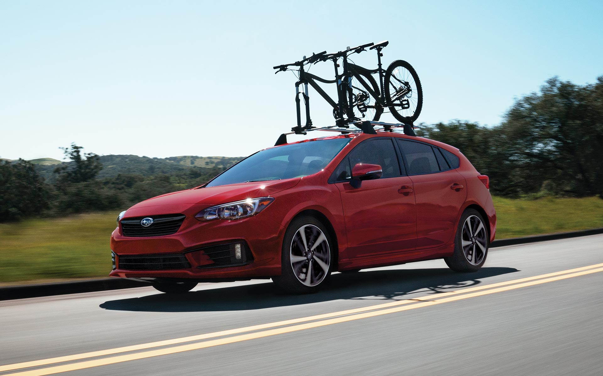 A 2020 Impreza sedan equipped with a bike rack driving down a highway.