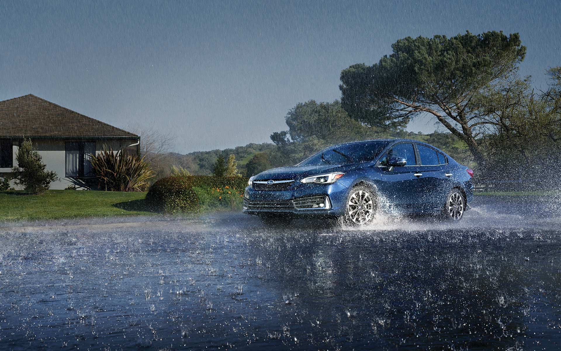 A 2020 Impreza sedan driving through a rain storm.