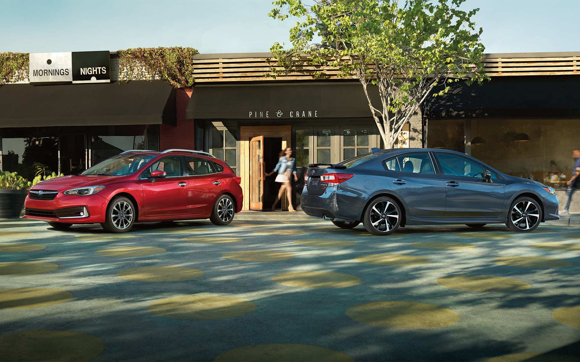 A photo of a 2020 Impreza 5-door and sedan parked outside of a restaurant.