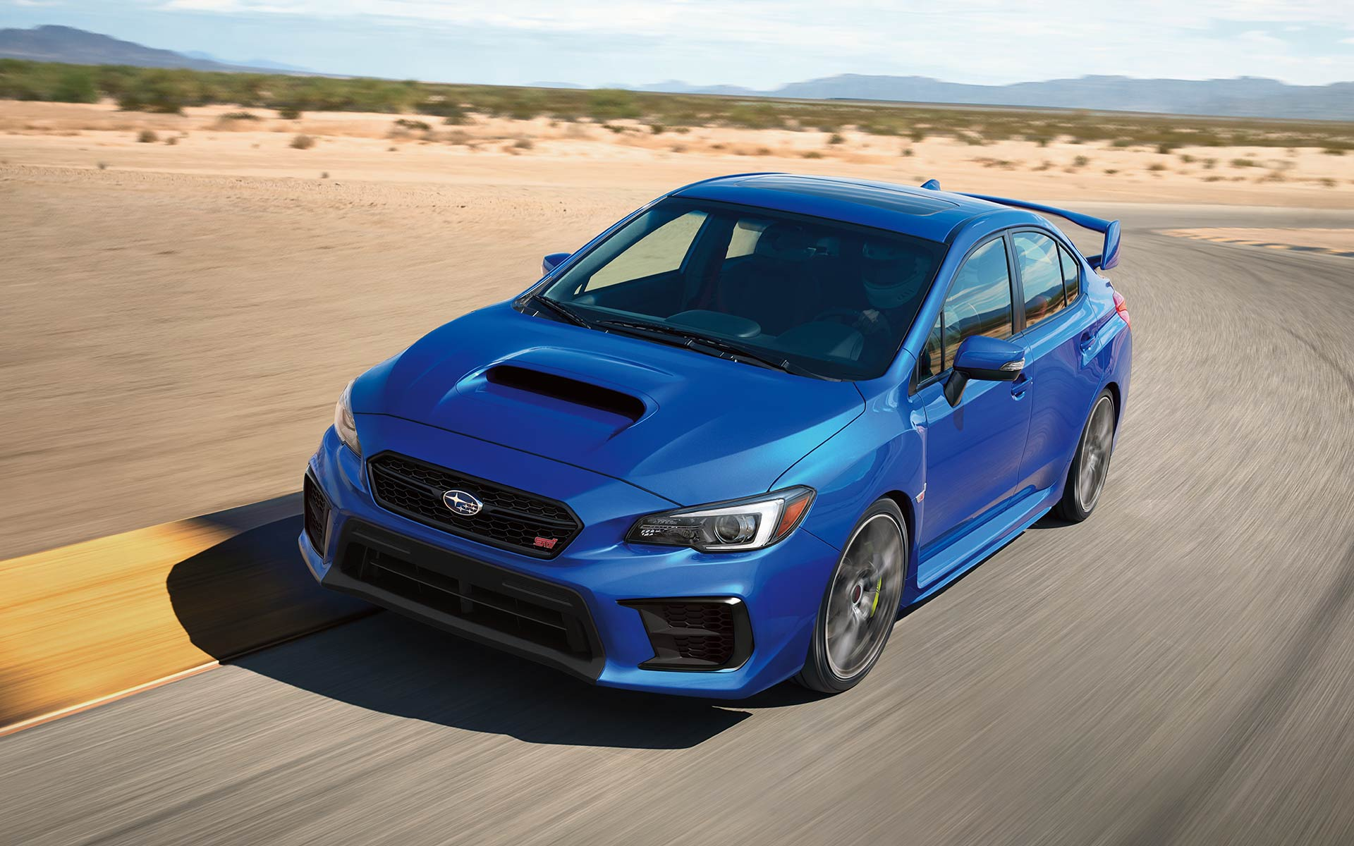 2020 WRX STI driving on track with desert and mountains in back