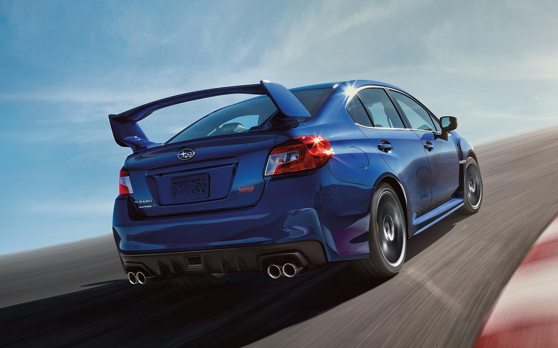 2020 WRX STI driving on track with blue sky and wispy clouds