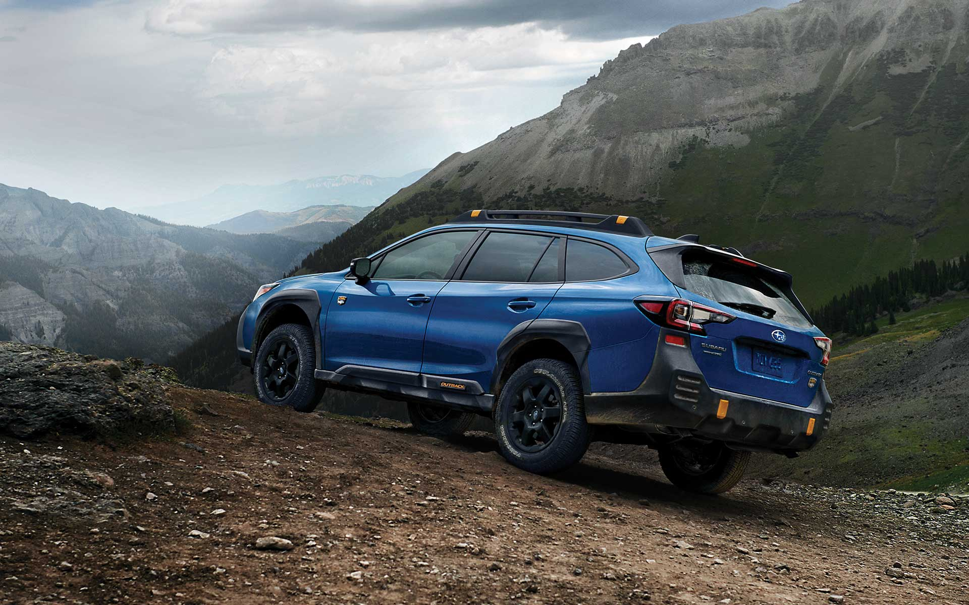 2022 Subaru Outback Wilderness driving up a rocky incline.