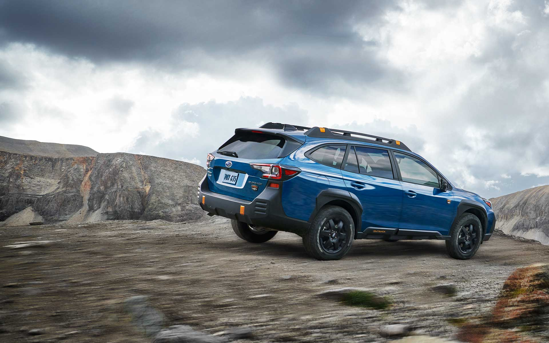 2022 Subaru Outback Wilderness driving down a rocky incline.