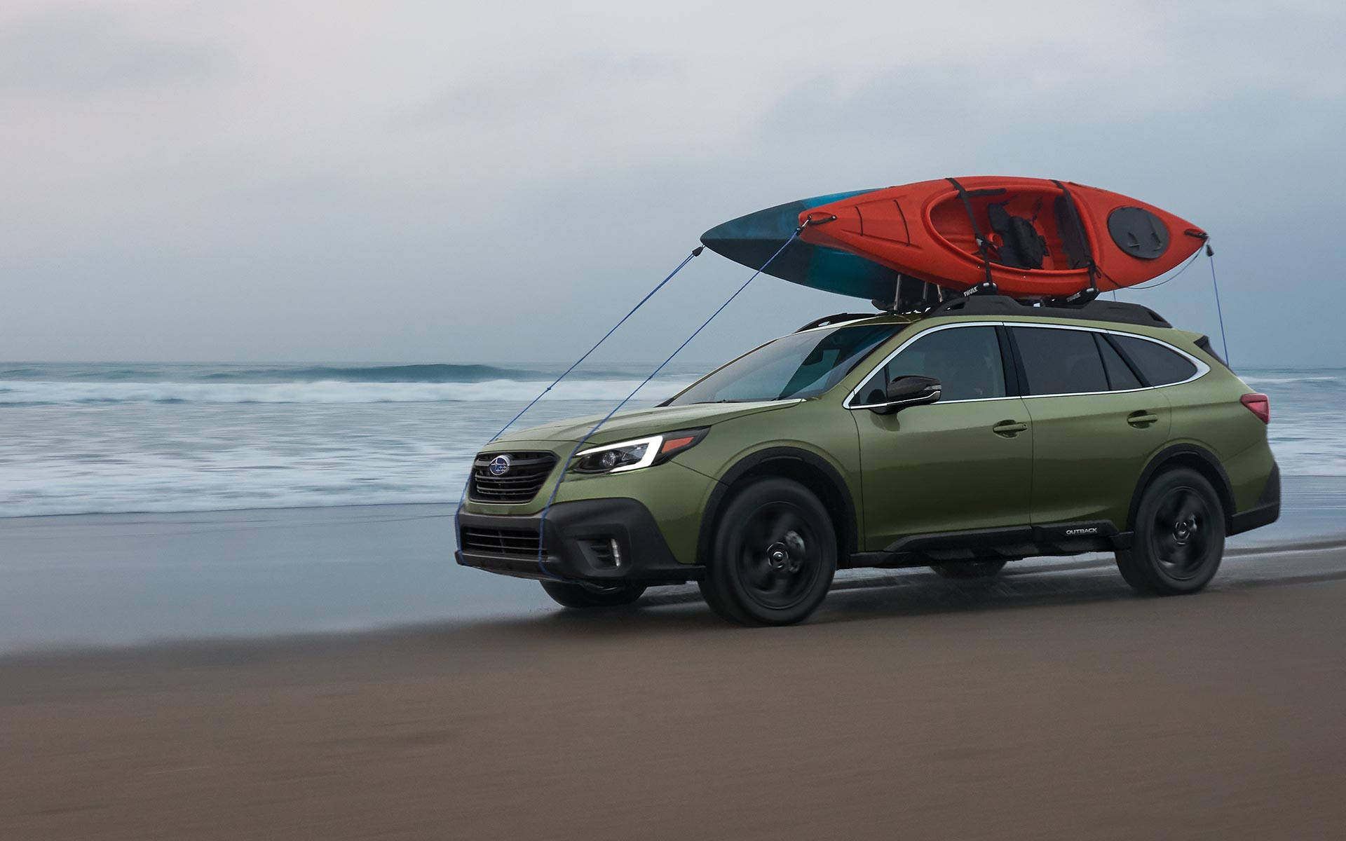 A 2022 Subaru Onyx Edition XT driving on a beach with kayaks mounted to its raised roof rails.